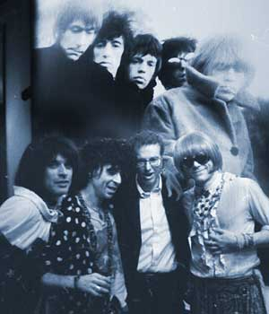 Photographer Gered Mankowitz poses with the band in front of one of his iconic images